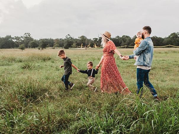 Family Walking Through Grass